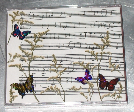 "Photocopied sheet music, pressed flowers and holographic butterfly ""stickers""."