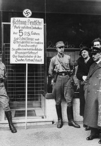 "Although by 1934 Germany had become a one-party state under Nazi rule, the increasingly reckless SA violence directed against Jews, communists, socialists and other dissidents began to offend the traditional German sense of civic order, especially in the senior leadership of the army.[1] The sign reads: ""Attention Germans! These Jewish owners of the 5 P.S. shops are the parasites and gravediggers of German trade! They pay German workers starvation wages! The principal owner is the Jew Nathan Schmidt."""