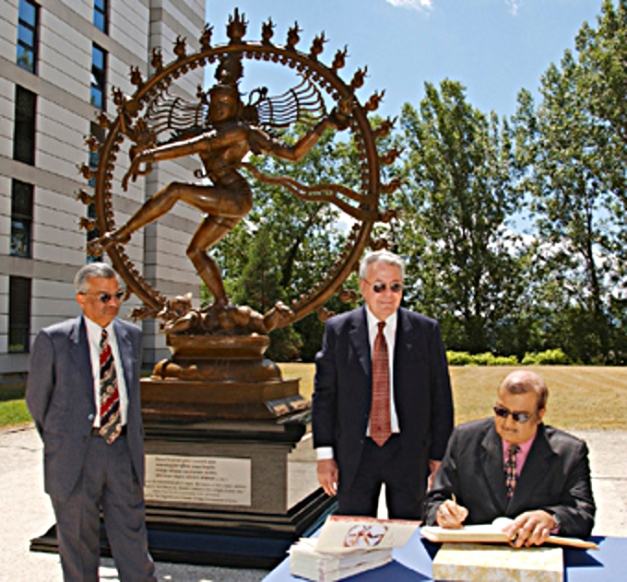 The Director-General and Dr. Kakodkar watch as Mr.Chandrasekhar signs the Guest Book. The statue is a gift from India, celebrating CERN's long association with India which started in the 1960's and continues strongly today. It was unveiled by the Director General, Dr Robert Aymar, His Excellency Mr K. M. Chandrasekhar, Ambassador (WTO-Geneva) and Dr Anil Kakodkar, Chairman of the Atomic Energy Commission and Secretary, Dept of Atomic Energy, India. In the Hindu religion, this form of the dancing Lord Shiva is known as the Nataraj and symbolises Shakti, or life force. As a plaque alongside the statue explains, the belief is that Lord Shiva danced the Universe into existence, motivates it, and will eventually extinguish it. Carl Sagan drew the metaphor between the cosmic dance of the Nataraj and the modern study of the 'cosmic dance' of subatomic particles. The statue was made in India. The original sculpture was a wax model, around which a soil mould was made. Melting the wax left a hollow into which liquid metal was poured. Once cooled, the mould was split and the statue polished and given its antique finish. The statue is on permanent display in the square between buildings 39 and 40, a short distance from the Main Building.